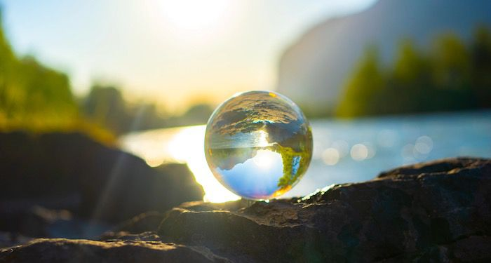 a photo of a clear marble positioned in front of a beautiful lake with mountains and trees in the background; the marble is reflecting and flipping the surroundings and it looks like a tiny planet earth
