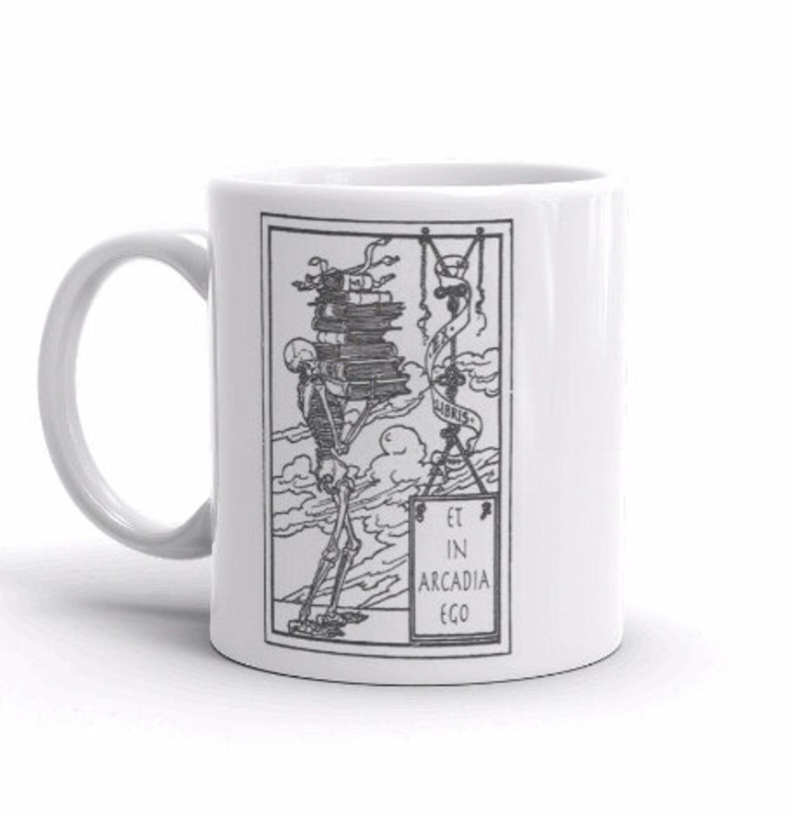 """Image of a white mug. The design on the mug features a skeleton holding books, with a sign reading """"et in arcadia ego."""""""