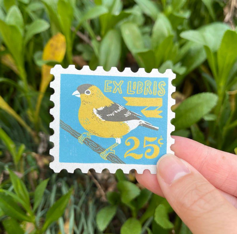 """A sticker styled to look like a blue stamp with an illustrated goldfinch that reads """"ex Libris"""""""