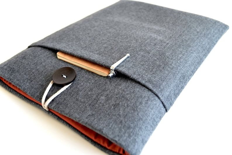 A gray herringbone reader sleeve with a button enclosure, orange lining, and an outside  pocket.