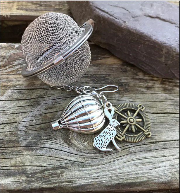 ball tea infuser with three charms on it: a hot air balloon, a rabbit, and a compass rose