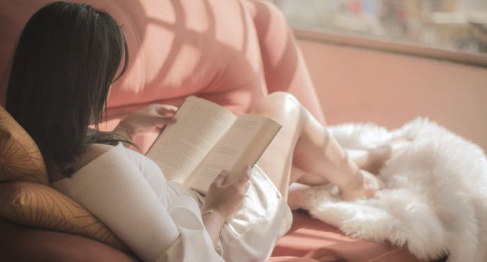 a woman reading a book sitting on a pink couch