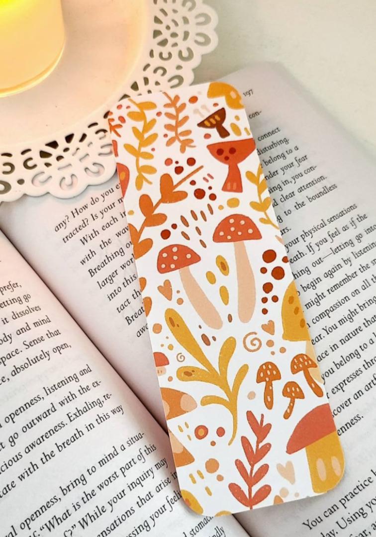Image of illustrated mushroom bookmark in oranges and reds.