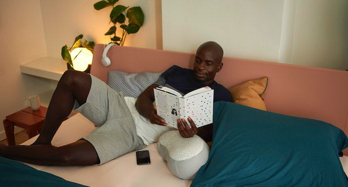 Image of a Black man reading a book on a bed.