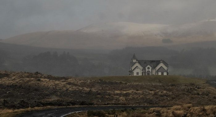 Image of a lone white house on a deserted road