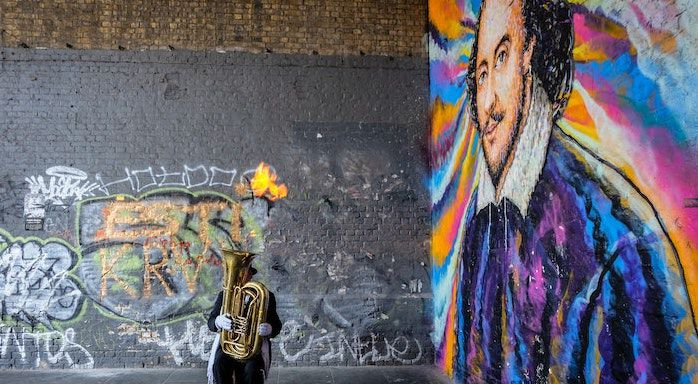 Image of tuba player in front of shakespeare painting