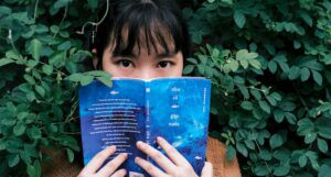 Image of an Asian woman with a book in front of her face