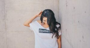 """Image of a woman with brown skin against a cement wall, with a shirt reading """"resilient"""""""