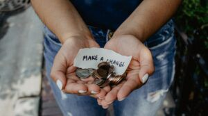 """image of hands holding change and note reading """"make a change."""""""