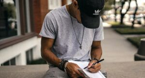 Image of brown skinned person with notebook and pen sitting outside