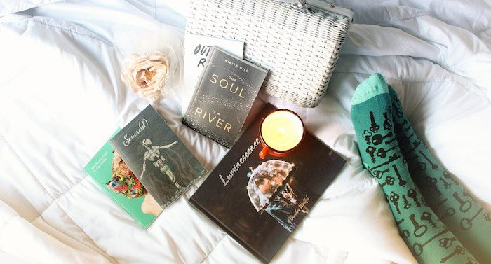 Image of poetry books on a sheet with green socked feet beside them.