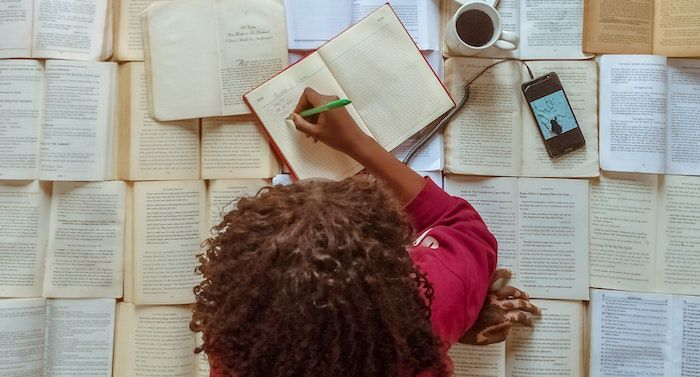 Image of top of woman's head who is on top of a pile of books and writing in a notebook
