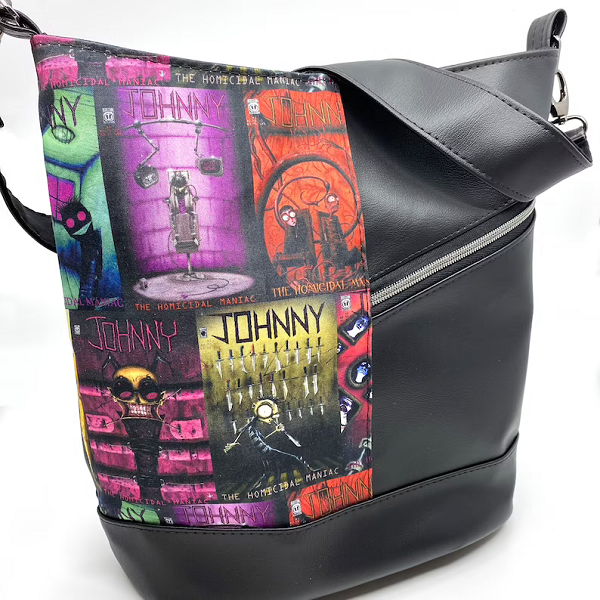 A faux leather handbag.  One half is black and the other half is a colorful composite of Johnny the Homicide Maniac comic book covers.