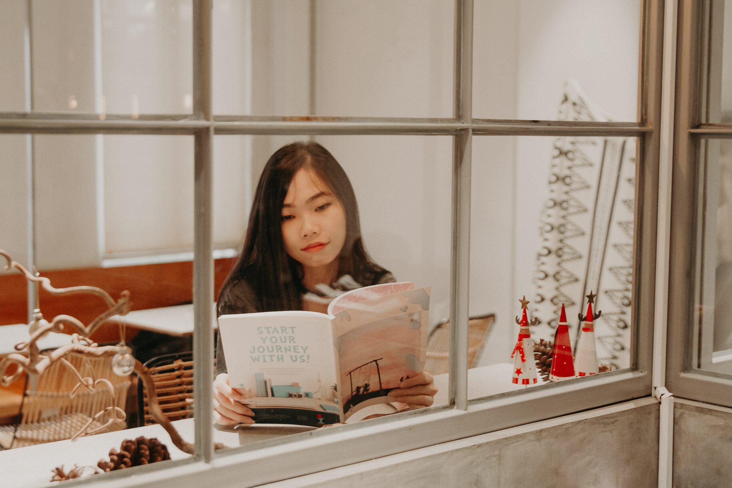 Asian woman reading a book near window