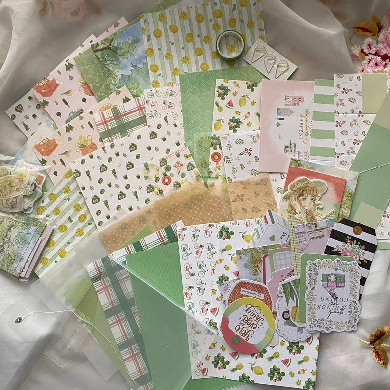Stationary kit with numerous papers in a range of yellow and green shades and patterns.