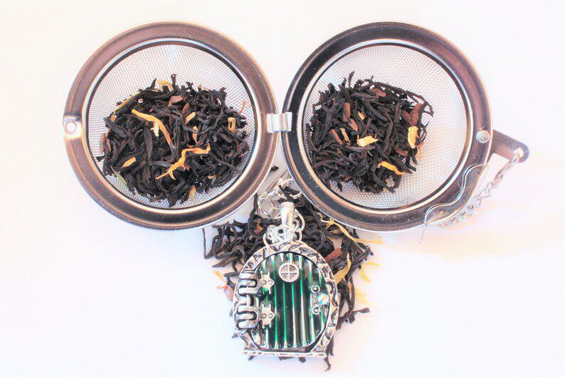 image of a ball style tea infuser with a green rounded hobbit door as a charm