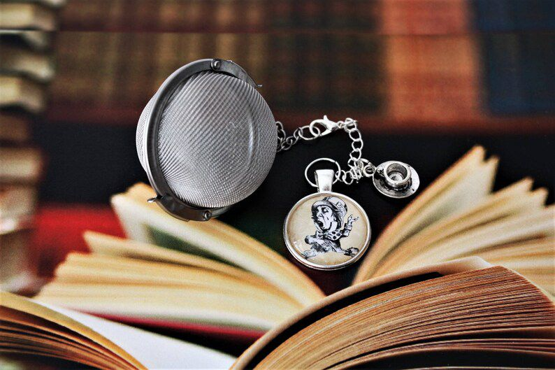 ball style tea infuser with a tea cup charm and a cabochon with an image of John Tenniel's Mad Hatter from Alice in Wonderland