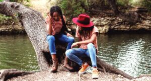 two young women sitting on a tree trunk by a body of water
