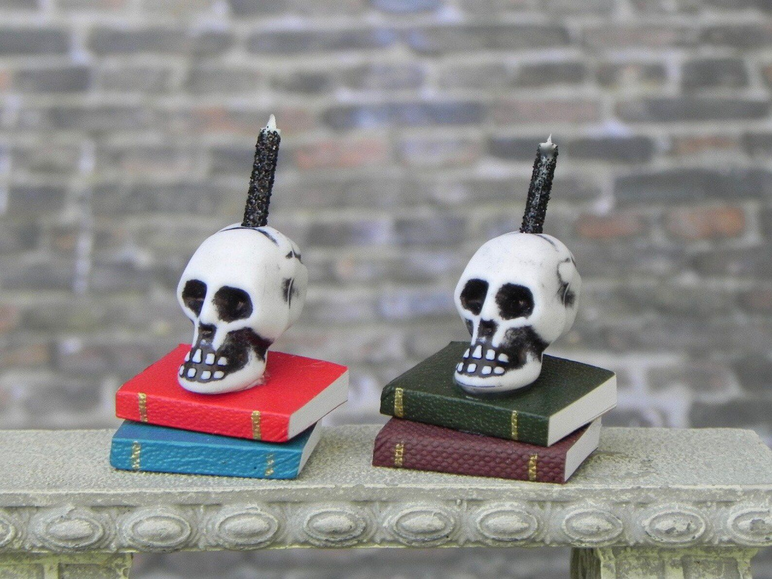 Image of two mini candles. They each have two miniature books, with a small skull on top.