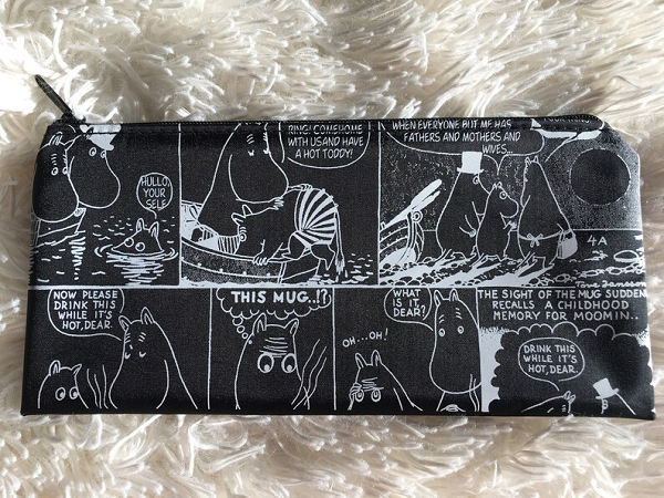 A black and white pencil case with signs from the Moomintroll comics.