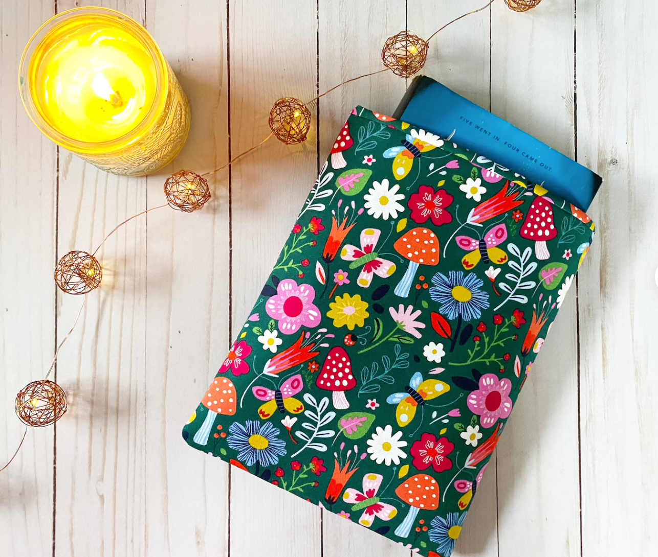 Image of a green book sleeve covered in mushrooms and flowers in bright colors.