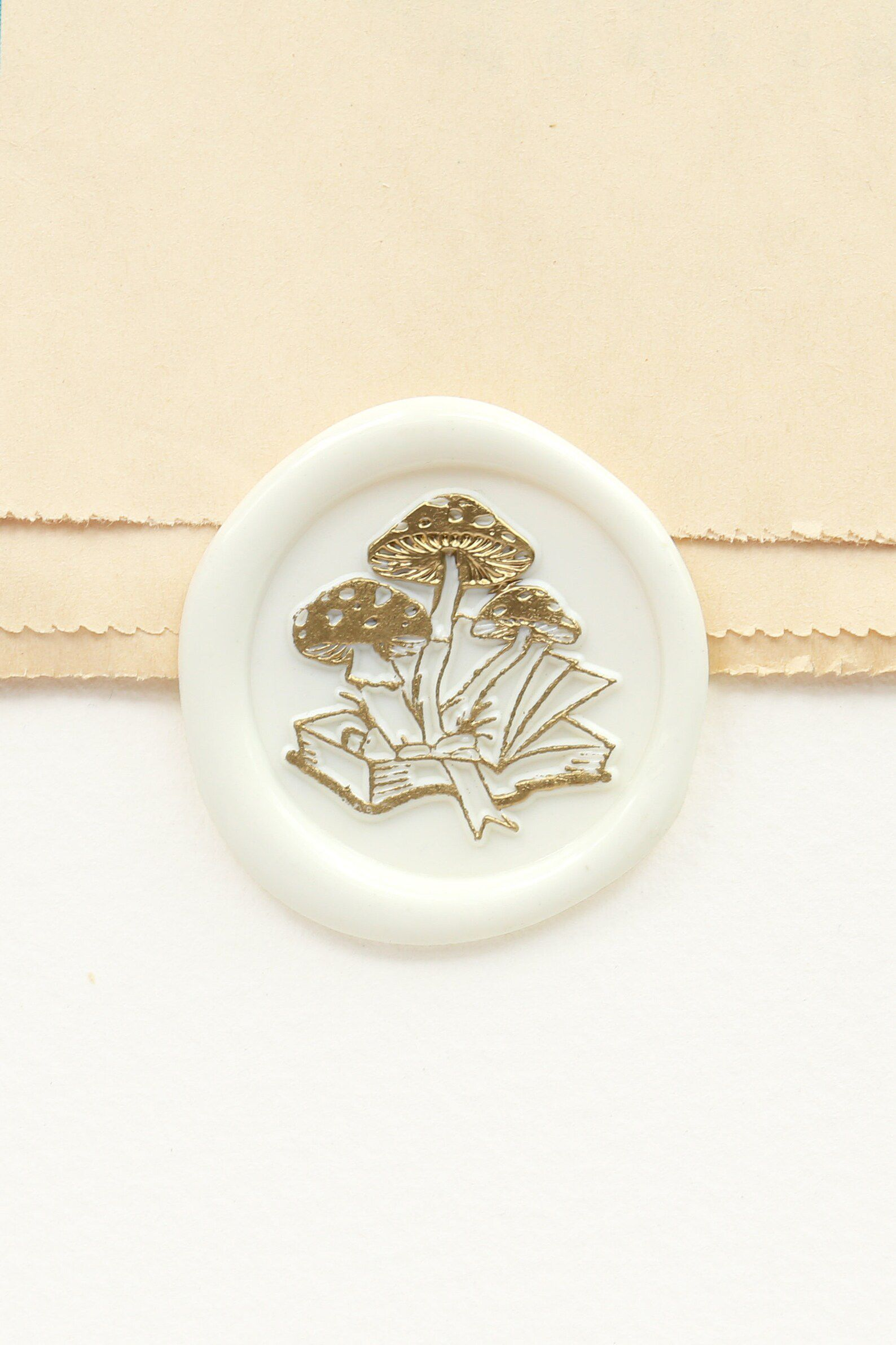 Image of white wax seal that includes a book and mushrooms.