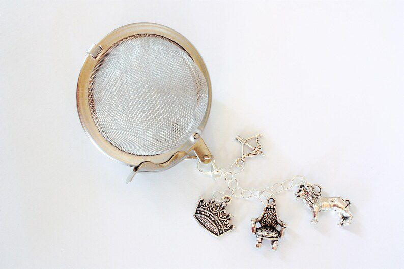 ball style tea infuser with charms of a crown, throne, lion, and bow and arrow, all silver.