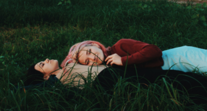 a woman lying in a field with another woman laying her head on her stomach