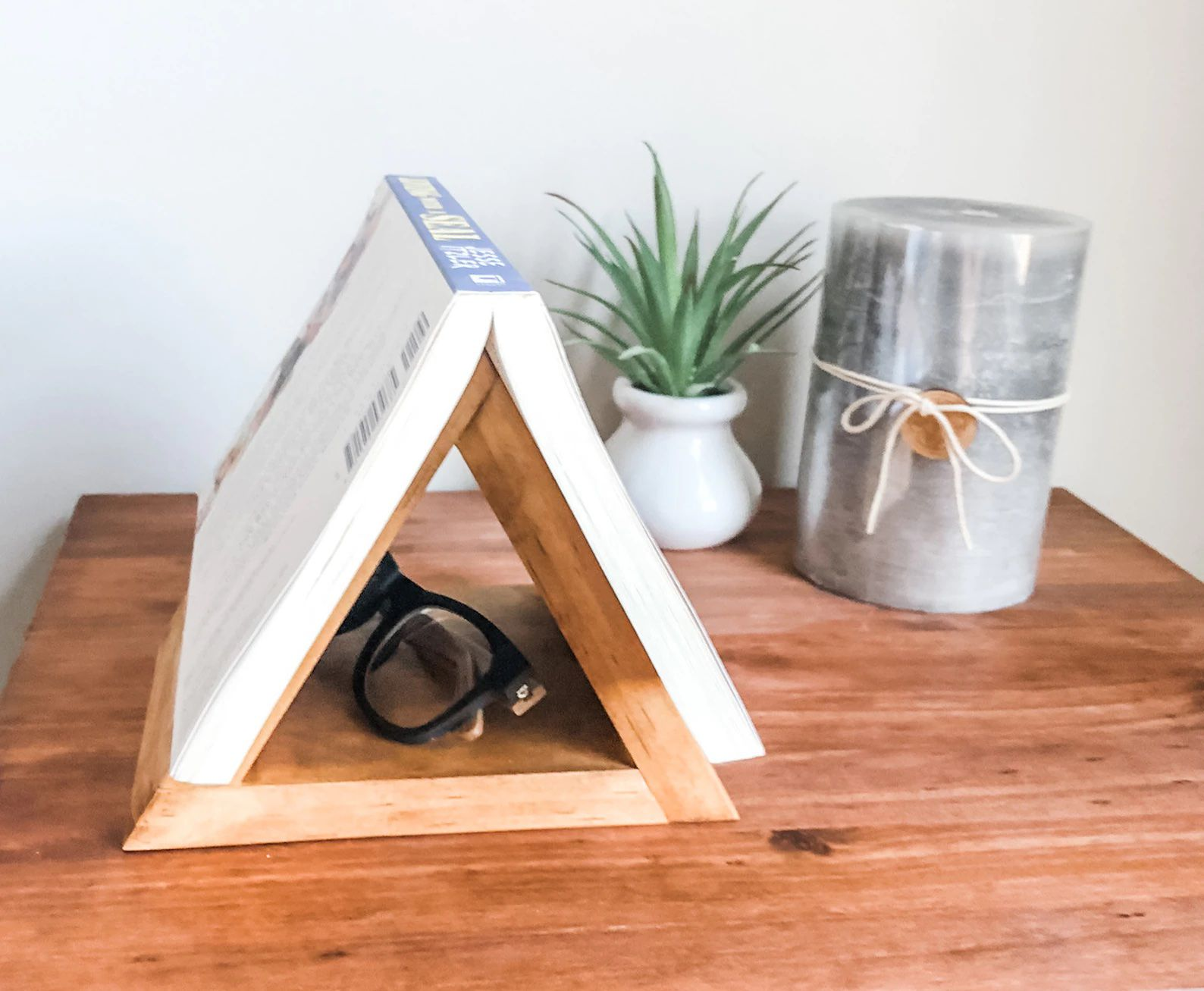 A triangular book holder sits on a nightstand, and a book is set down, open, on top of the holder so the pint of the triangle holds the book open. It's displayed on a nightstand with a candle and plant.
