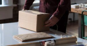 person packing up a cardboard box, assorted packing supplies strewn next to them on a white table