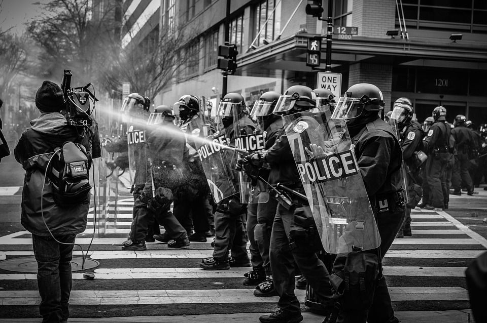 Black and white image of a line of police in riot gear, carrying shields, walking in a road in a city. One of the police officers is spraying pepper spray towards a person with a backpack and video camera