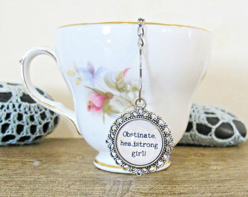 """image of a pride and prejudice tea infuser in a white mug with the quote """"obstinate headstrong girl"""" on the infuser charm"""