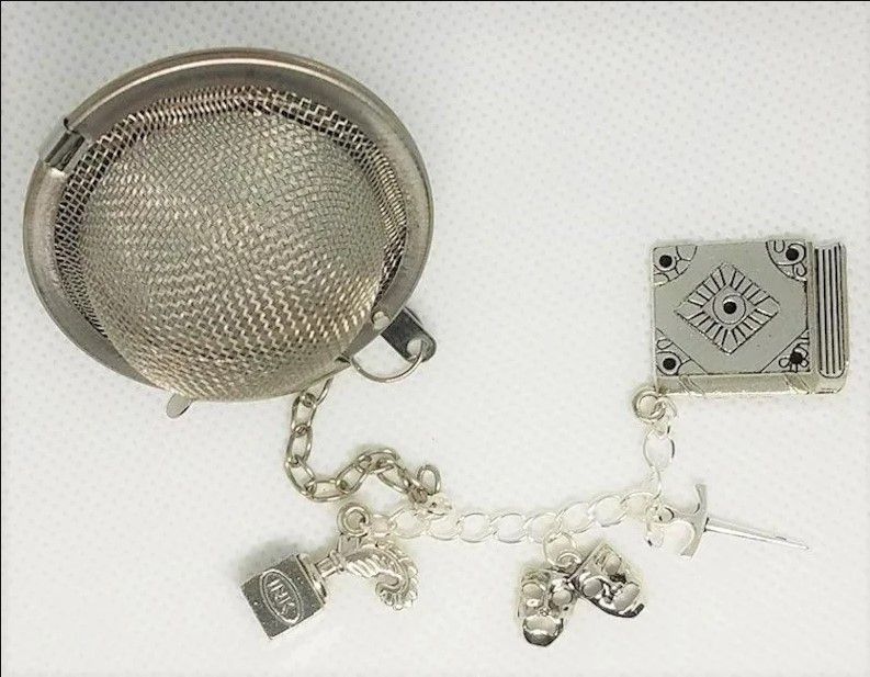 ball tea infuser with a chain of silver charms: an ink pot with a quill in it; a set of theatre tragedy masks; a dagger; and a closed book.