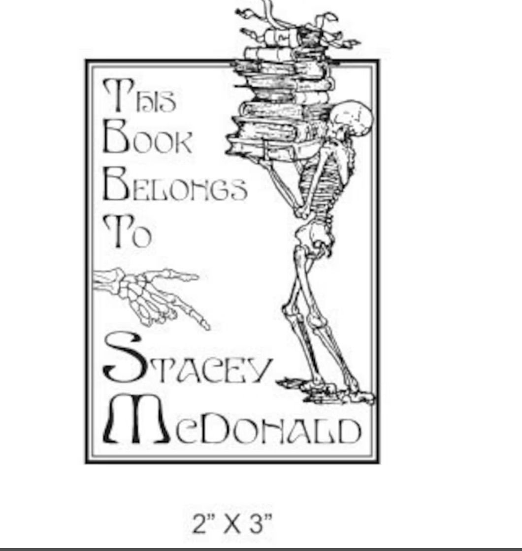 """Image of a bookplate. The left side reads """"this book belongs to,"""" while the right features a skeleton holding a stack of books."""