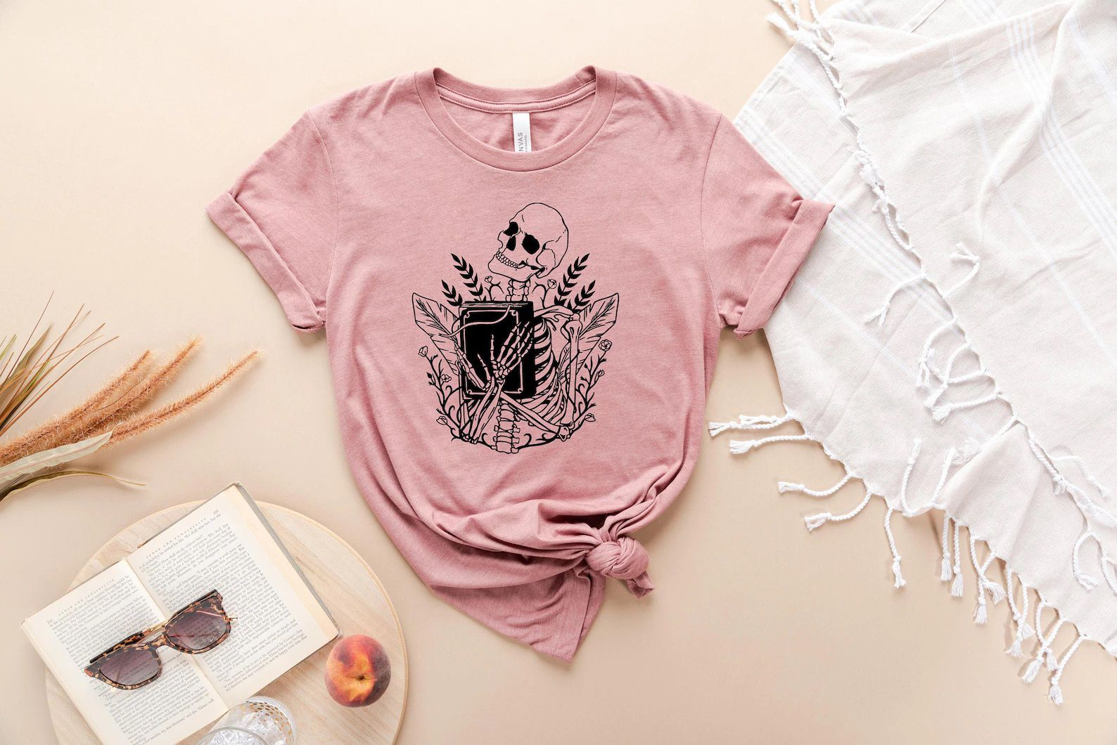 Pink t-shirt depicting a black line art drawing of a skeleton clutching a black book to its chest with a background of plants.