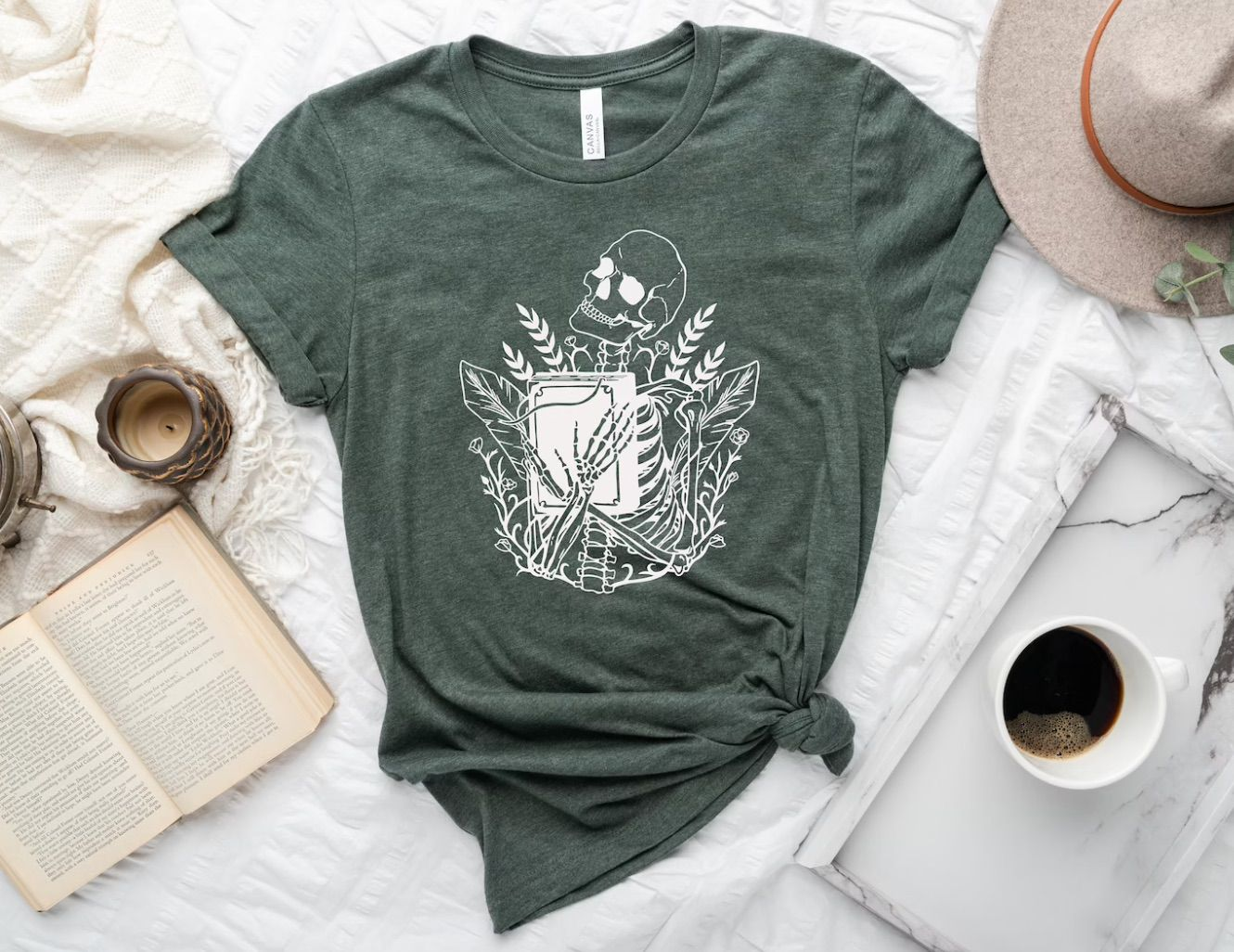 Heather gray t-shirt with a white skull hugging a book.