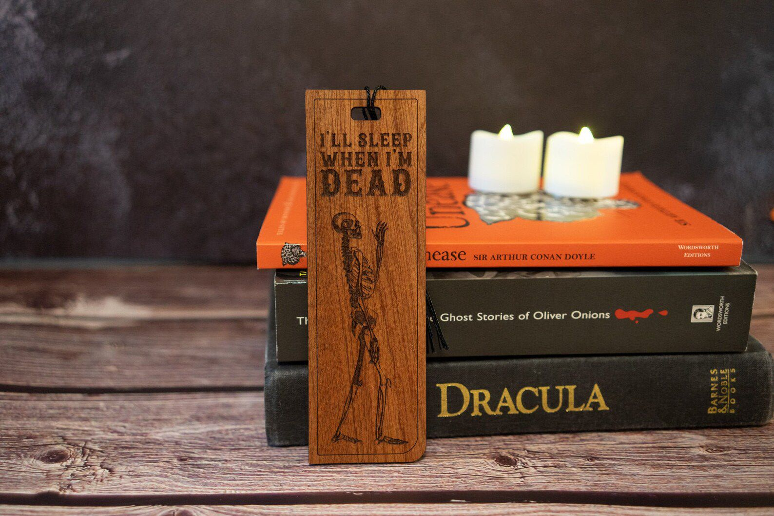 """Image of a wooden bookmark with a skeleton. Above the skeleton, it reads """"I'll sleep when I'm dead."""""""