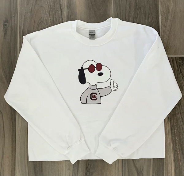 A white sweatshirt with Snoopy.  Snoopy is in his character as Joe Cool, wearing a University of South Carolina sweatshirt and giving a thumbs up.