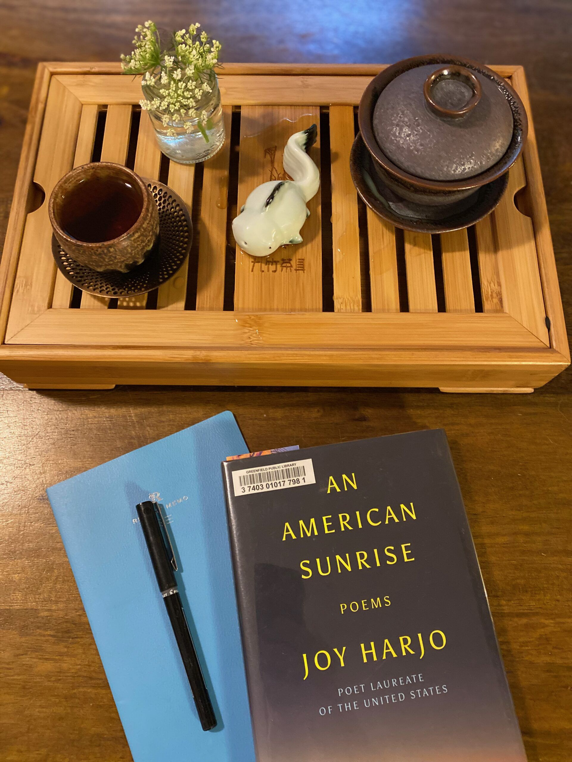 A tea setup on a wooden tray with open slats: a small ceramic mug on a metal coaster, a goldfish tea friend, a small jar of Queen Ann's lace, and a small Gaiwan teapot. A blue notebook and An American Sunrise by Joy Harjo sit on the table in front of the teaware. Photo by me.