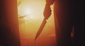 a hand holding what appears to be a bloody knife