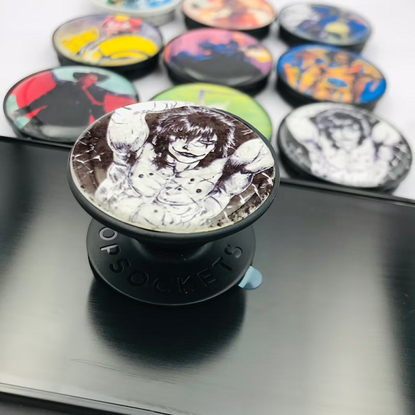 A small arrangement of Pop Sockets, blurry.  In the foreground, in the center, is a Pop Socket with the comic book version of The Crow.