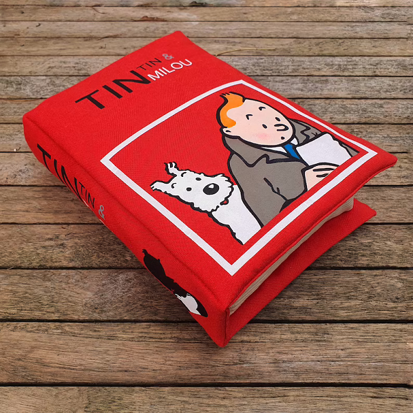 A thick red pillow made to look like a Tintin book with TinTin and Snowy on the cover.