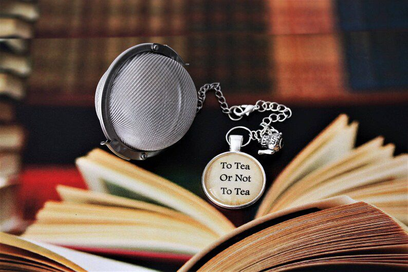 ball style tea infuser with a little tea mug charm and a cabochon that says to tea or not to tea