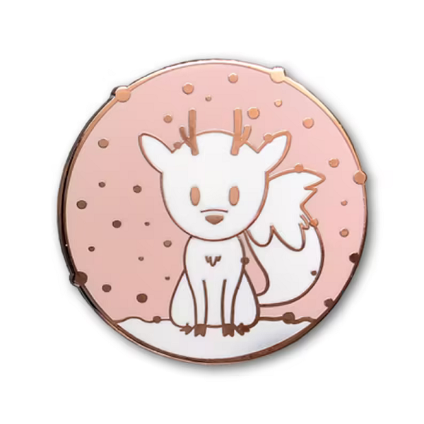 A pink, white and rose gold enamel brooch with Twig the Deerfox sitting in the snow.