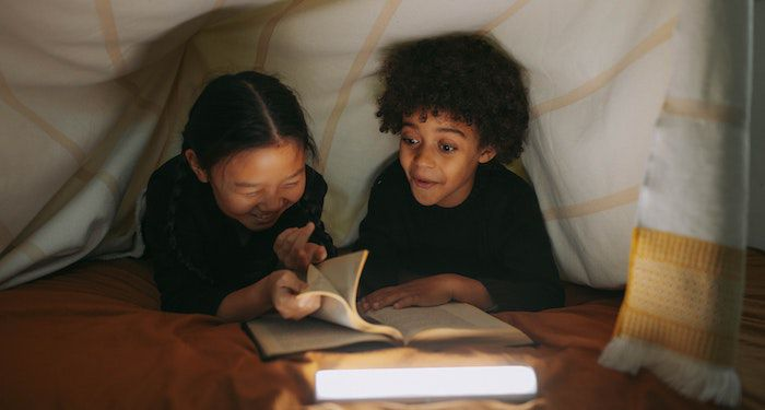 two kids reading in blanket fort