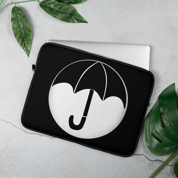 A black and white laptop sleeve with the Umbrella Academy logo on it.