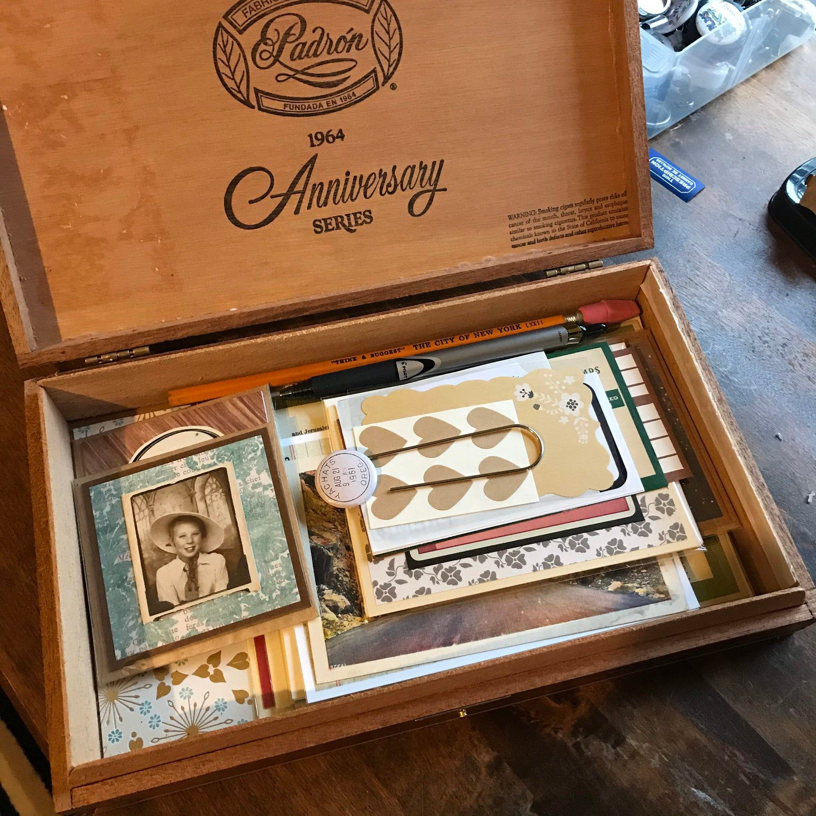 Image of cigar box with vintage style stationary inside, including pencils and pens.