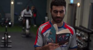 in a still frame from Ted Lasso Roy is reading a copy of A Wrinkle in Time
