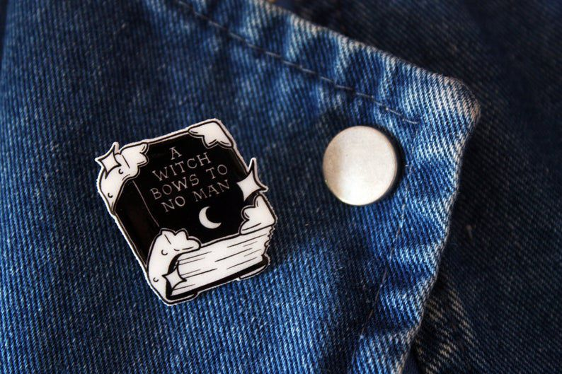 """Enamel pin in the shape of a book reading """"A witch bows to no man."""""""