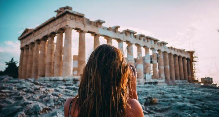 image of woman looking at ancient greek ruins